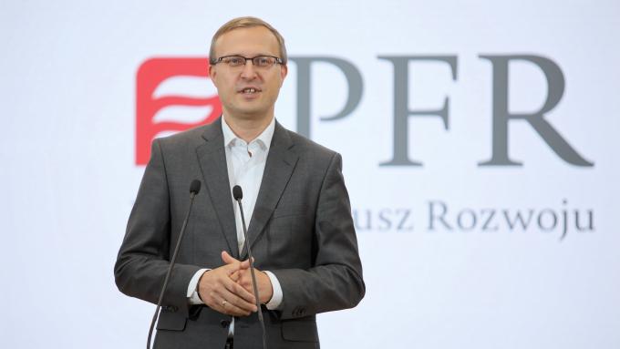 Prezes zarządu Polskiego Funduszu Rozwoju S.A. Paweł Borys na tle ścianki z logo PFR