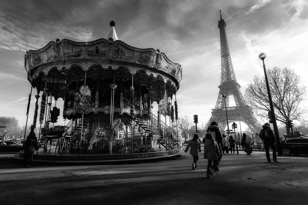 Czarno białe zdjęcie z wieżą Eifflai karuzelą